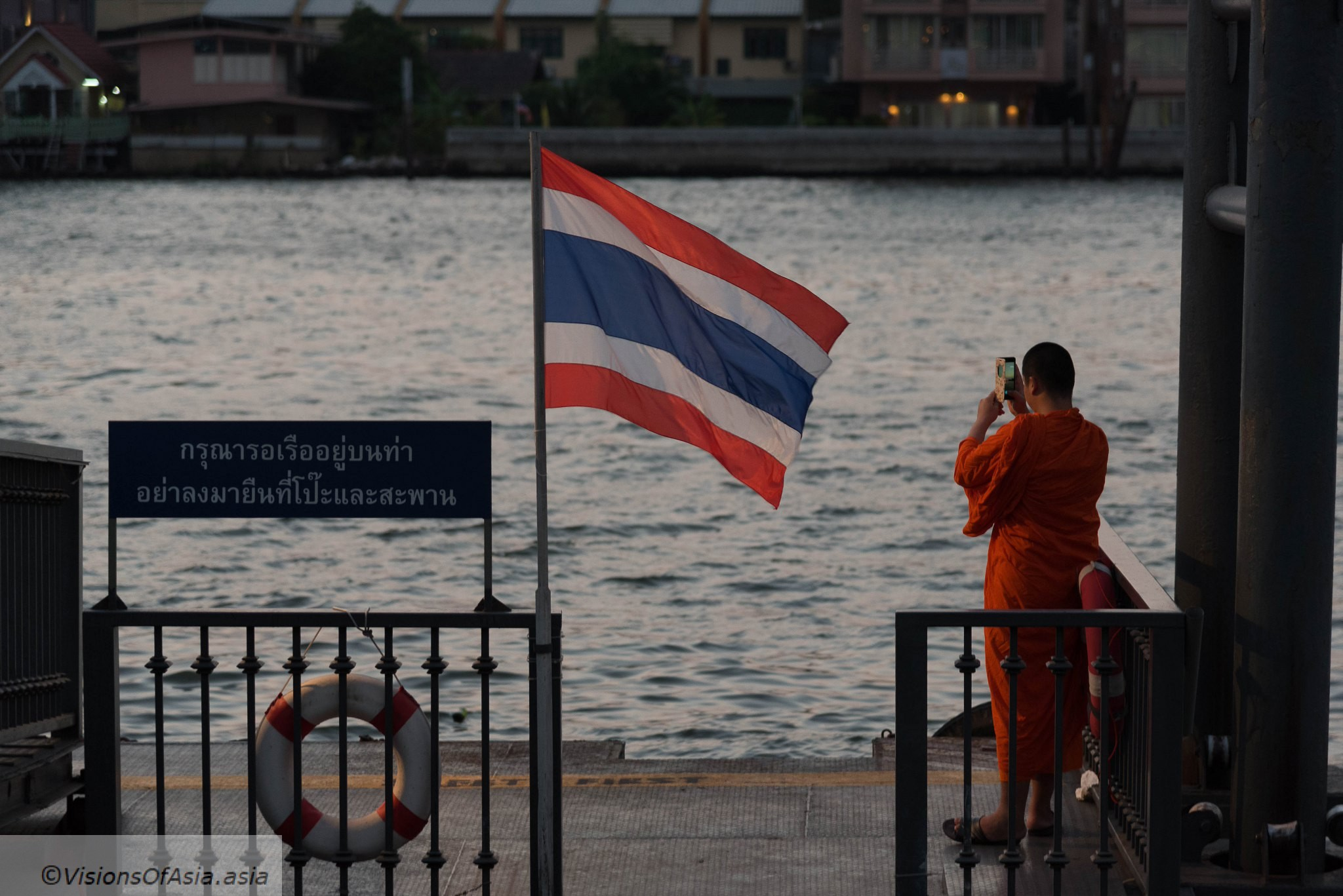 Thailand today: a monk, a smartphone and a flag