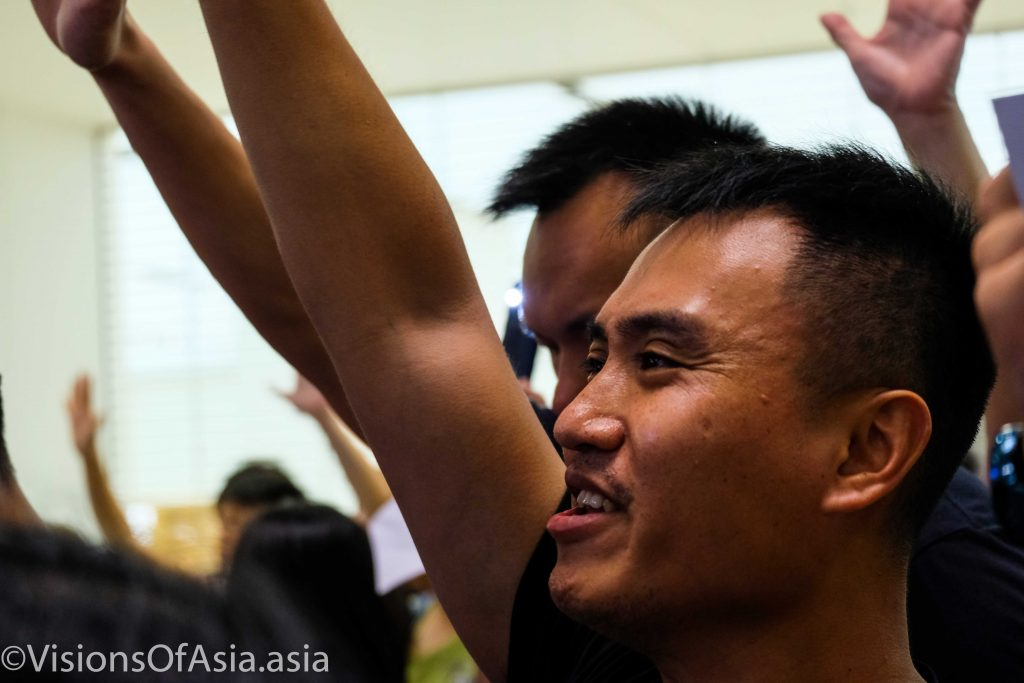 A protester chants with others, while raising his five fingers