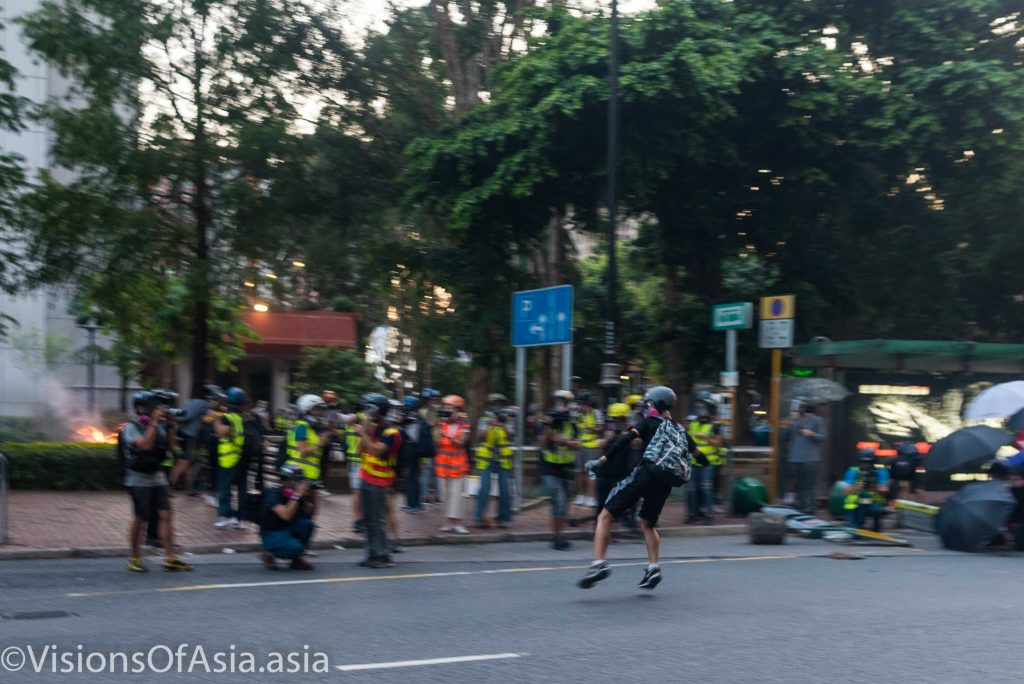 A protester throws an object on the police