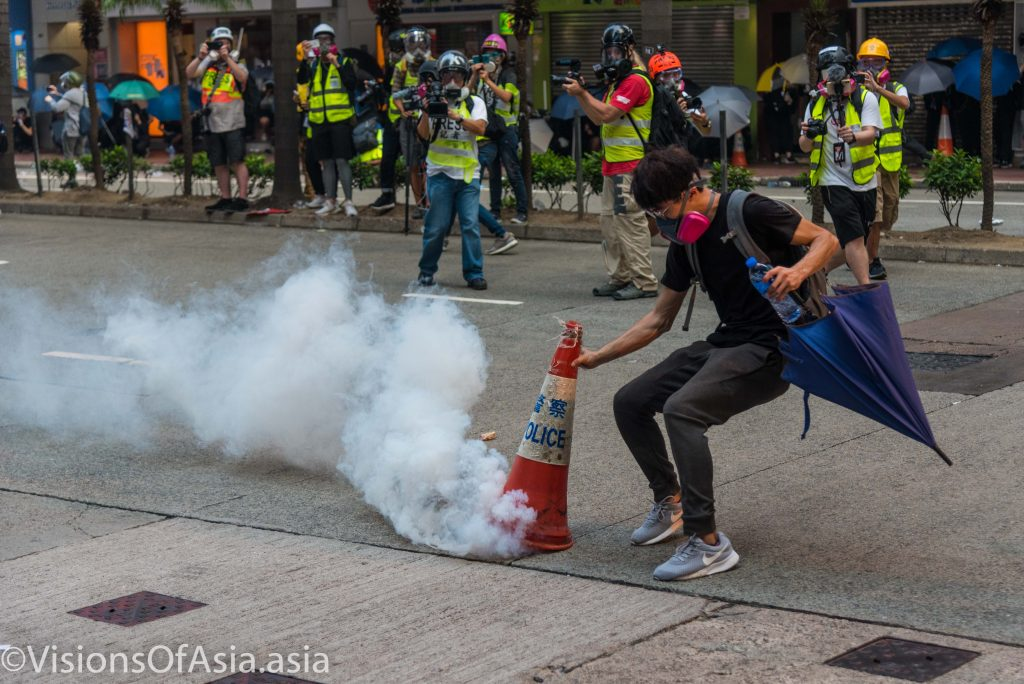 A protester extinguishes a canister of tear gas