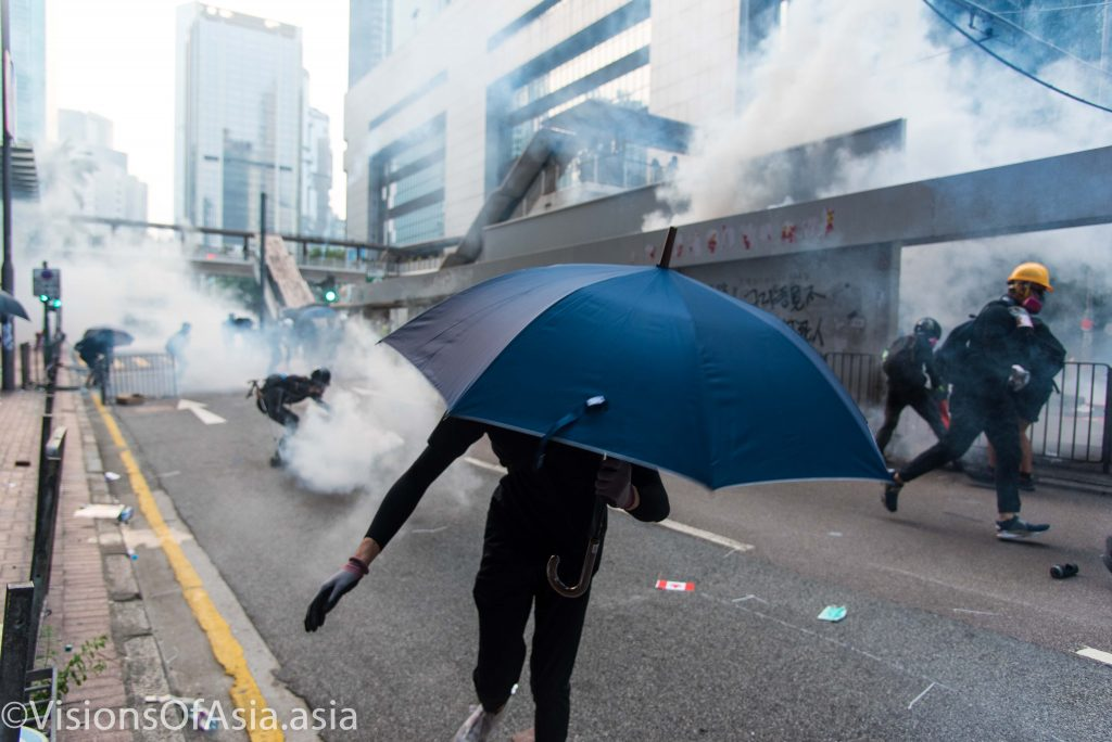 A protester retreats from the tear gas