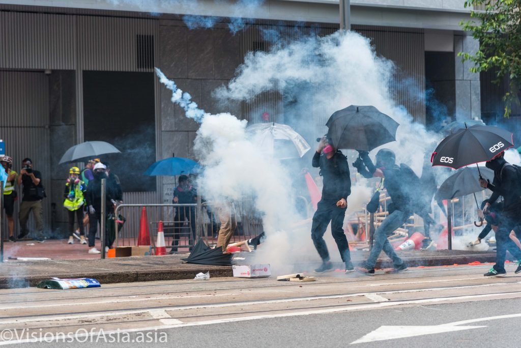 A protester hits back a tear gas canister
