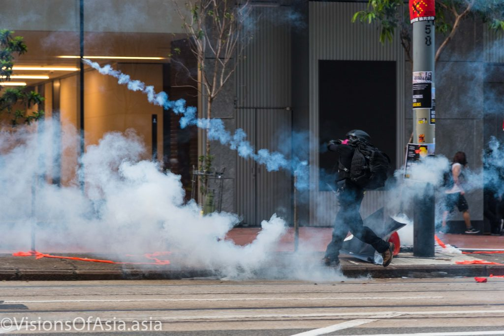 A protester throws back a tear gas canister
