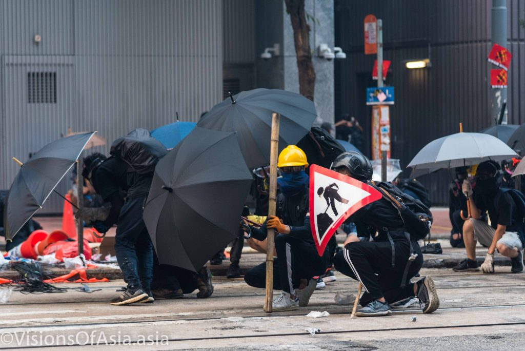 Protesters take shelter behind umbrellas near the police HQ