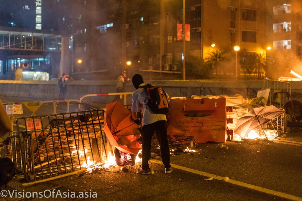 A protester feeds a blaze in Wong Tai Sin