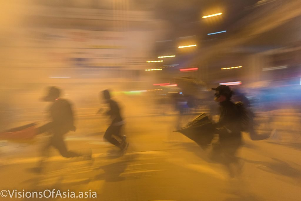 Protesters pull back in a cloud of tear gas
