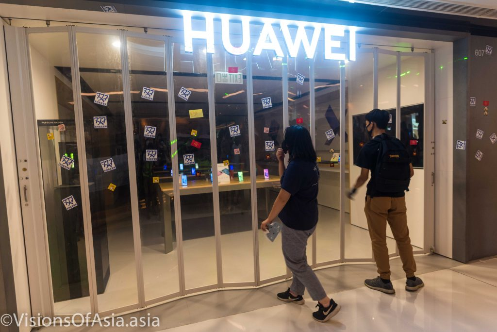 Protesters affix stickers on a Huawei shop in Shatin