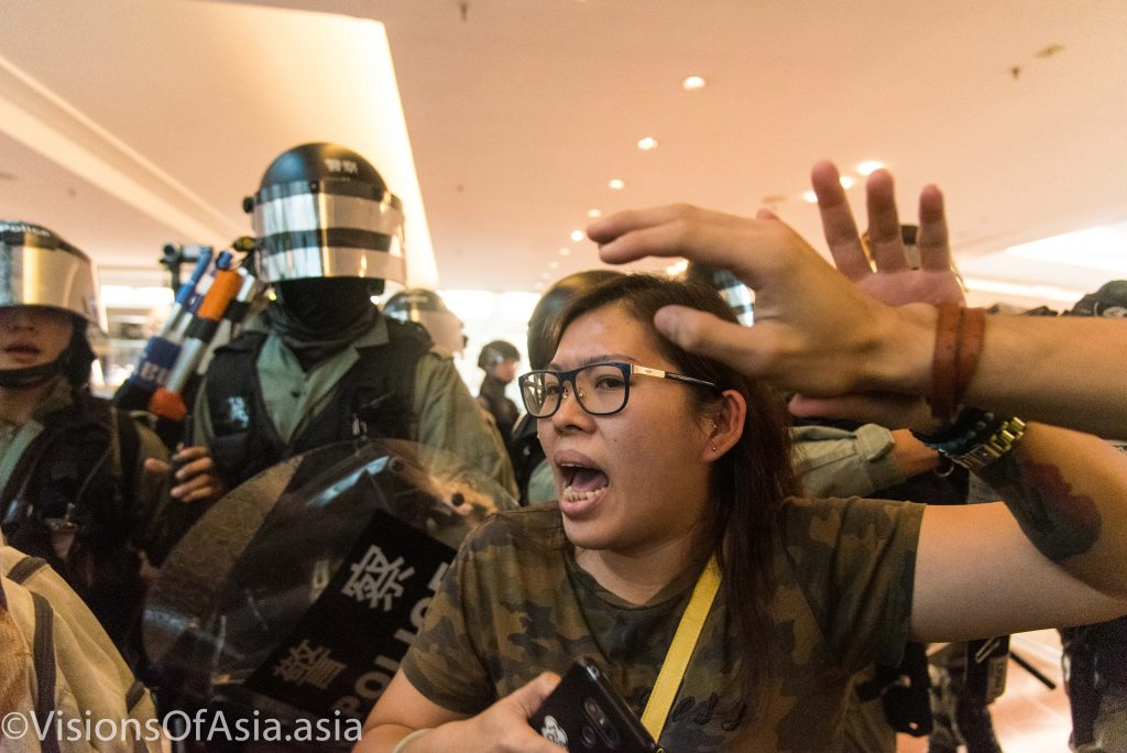 A protester is pushed ahead by riot police