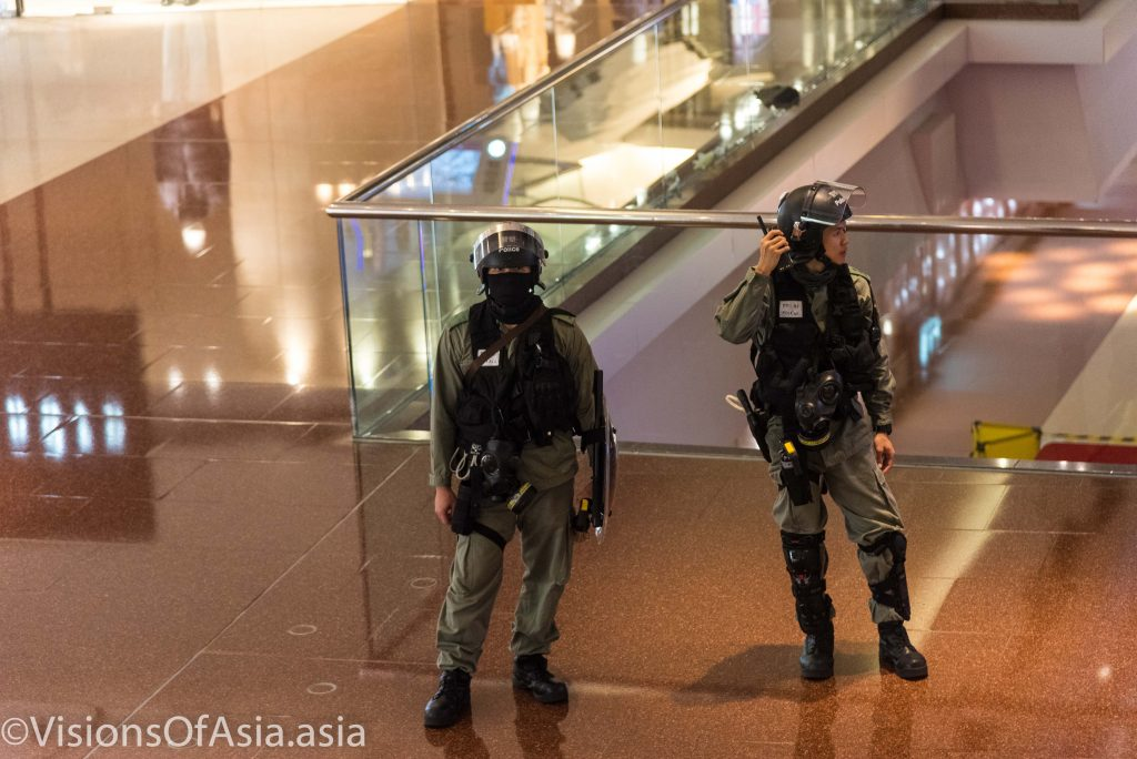 Police stand guard as they pushed back journalists out of the mall