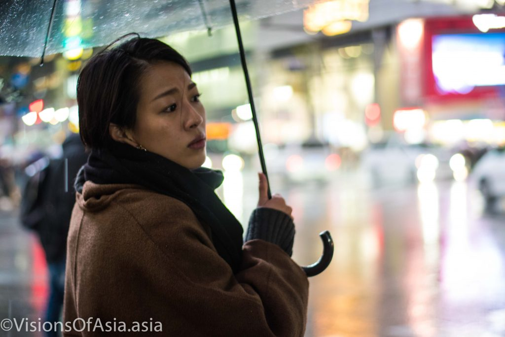 A young lady looks from under her umbrella as she is about to cross