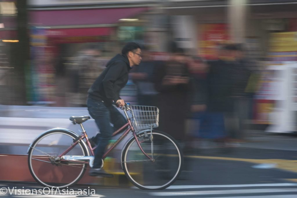 A guy biking through Asakusa