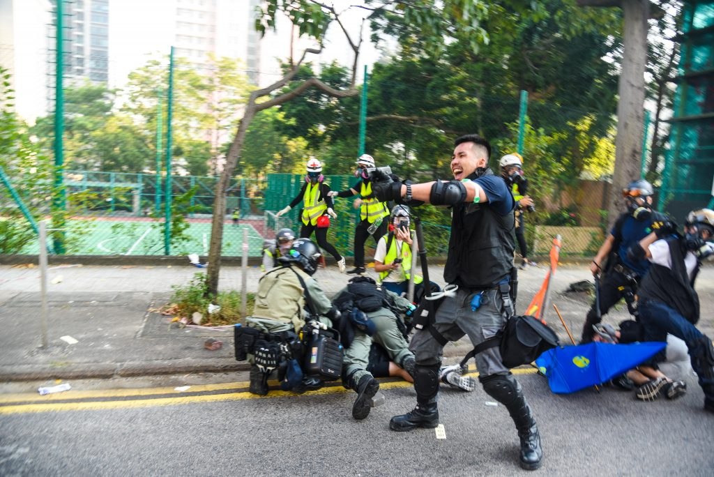 A policeman warns protesters not to advance