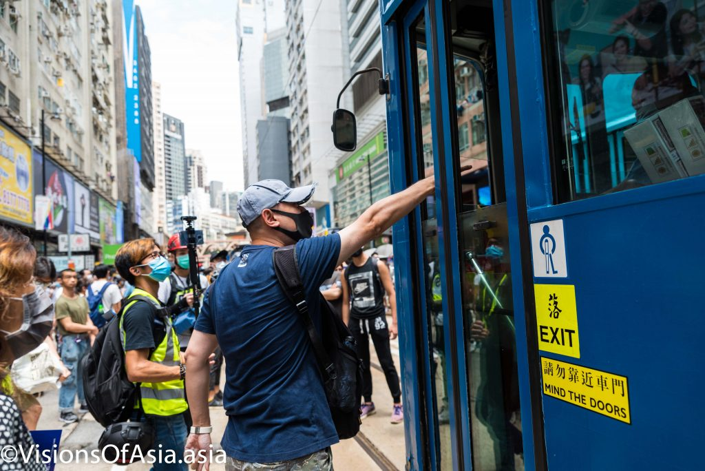 A protester angrily yells at a tram driver