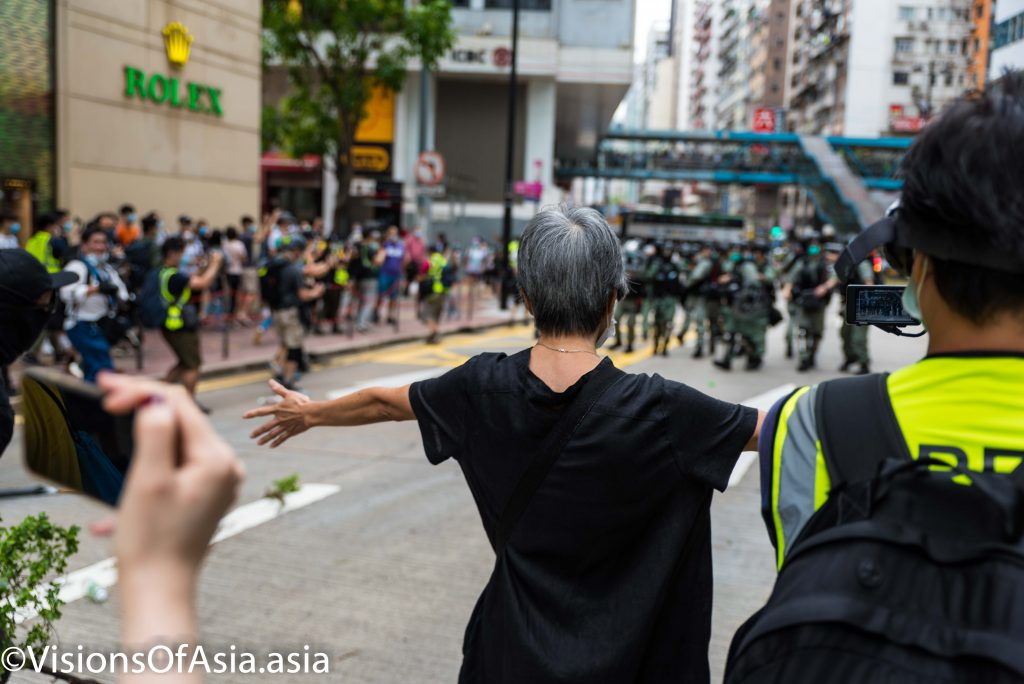 An old lady tries to interpose between riot police and protesters