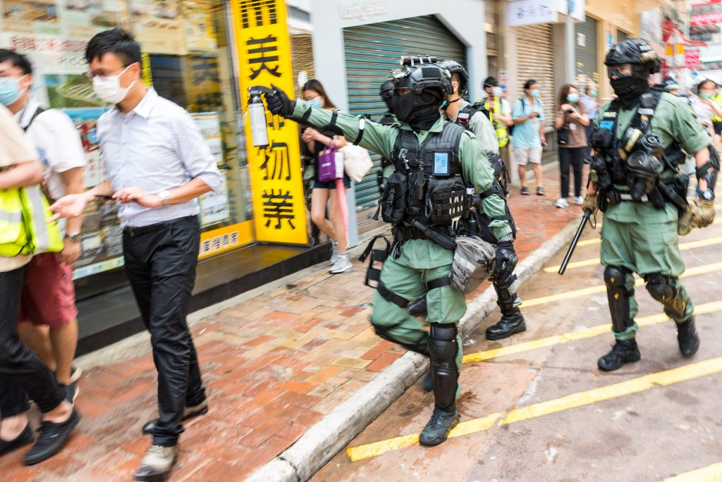 Riot police threaten protesters with pepper