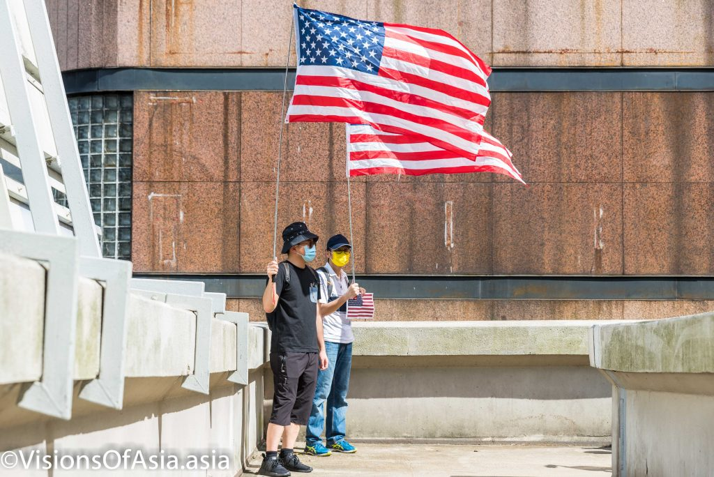 04 Jul 2020 Two protesters stand, holding American flags on an overpass in Central Hong Kong on July 4th.