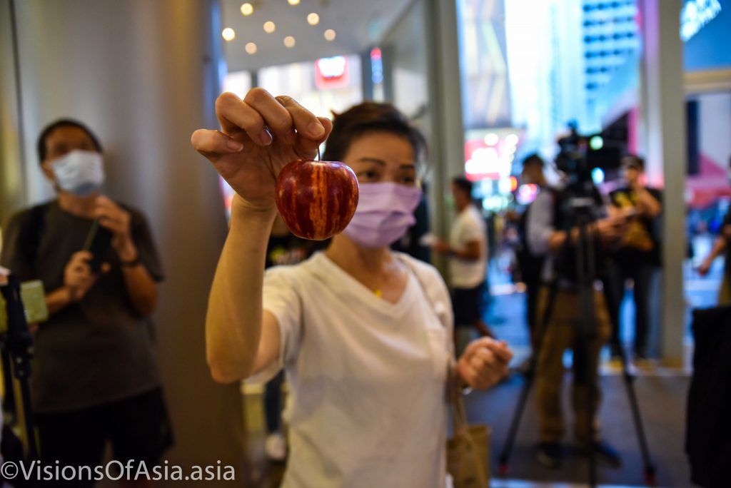 A lady shows an apple as sign of protest during a protest after the arrest of Jimmy Lai, the owner of Apple Daily.