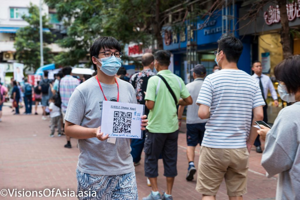 "Hong Kong,11 Jul 2020 A volunteer holds the QR code to download the voter app to vote at the pan-democrat primaries in Whampoa. The Hong Kong Governement denounced these primaries as a ""violation"" of the National Security Law, and the police raided the offices of the firm organizing the vote on the evening prior to the vote, thus delaying its start to 12.00 noon."